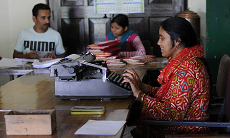 Image of a woman typing in an office in India. Photo by HPP India.